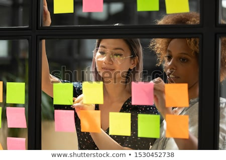 Two young multicultural female managers or office workers organizing work Stock photo © pressmaster