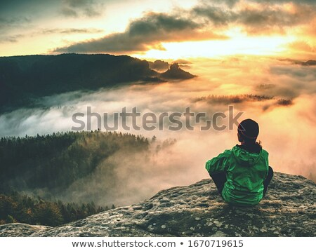 Mountain explorer taking in views from a rock precipice Stock photo © lovleah