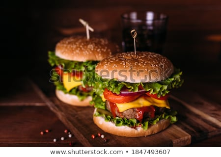 two tasty grilled home made burgers with beef tomato onion and lettuce stock photo © dash