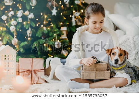Photo of lovely small child sits crossed legs on floor, pets pedigree dog received Christmas present Stock photo © vkstudio