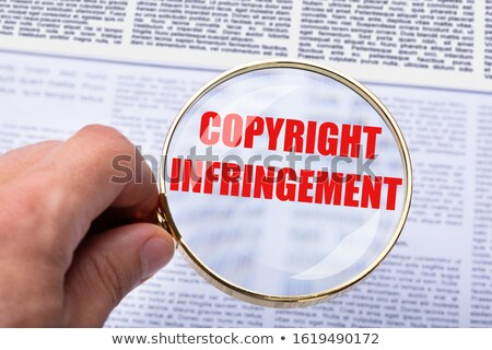 Person Holding Magnifying Glass Over Copyright Infringement Word Stock photo © AndreyPopov