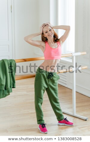 Red haired woman has perfect figure, keeps hands on head, feels tired after dance rehearsal, stands  Stock photo © vkstudio