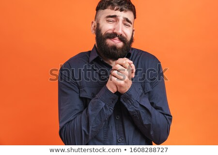 Image closeup of stressed man begging and keeping hands together Stock photo © deandrobot