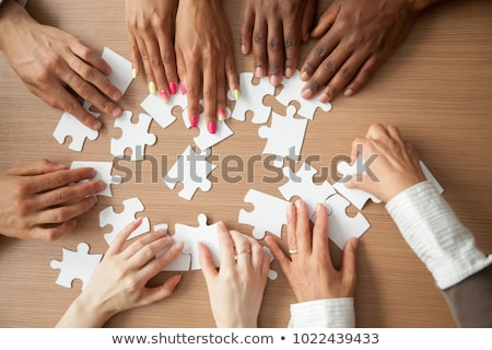 Businessman putting together jigsaw puzzle pieces Stock photo © Elnur