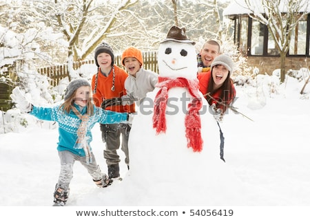 Stock photo: Father and daughter building snowman