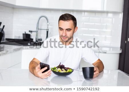 attractive young business man having a glass of juice in his hand stock photo © get4net