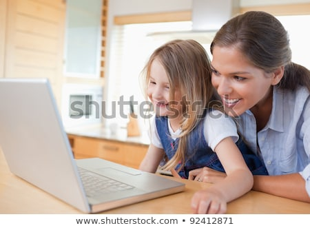 Mother and her daughter using a notebook in their kitchen Stock photo © wavebreak_media