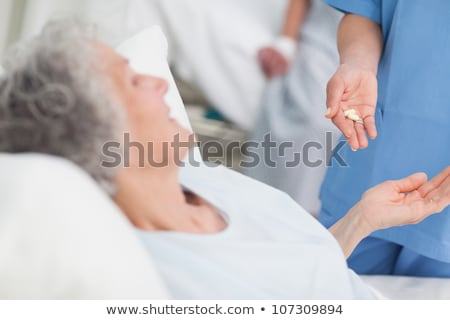 Nurse giving drugs to a patient in hospital ward Stock photo © wavebreak_media