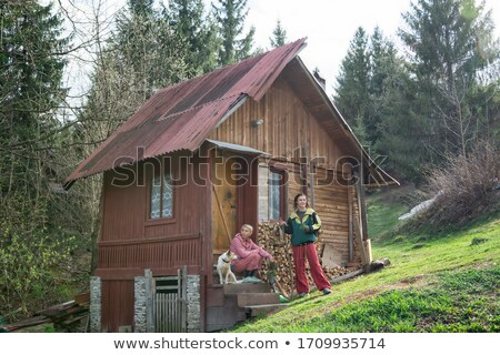 Beautiful young woman at an old rustic cottage Stock photo © konradbak