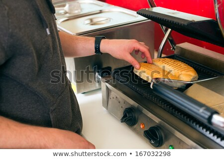 salesman making hotdog in fast food snack bar Stock photo © Kzenon
