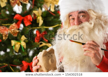 Authentic Santa Claus holding piggy bank and painting it Stock photo © HASLOO