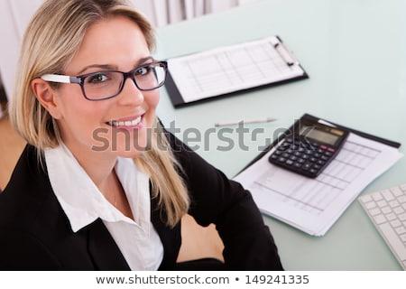 glimlachend · jonge · zakenvrouw · calculator · vergadering · bureau - stockfoto © cursedsenses