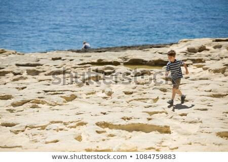 Boy playing with rocks on the coast Stock photo © bmonteny
