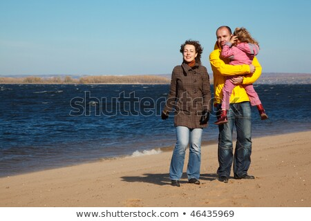 Parents with little girl walk on autumn beach. Productive leisure in open air. Stock photo © Paha_L