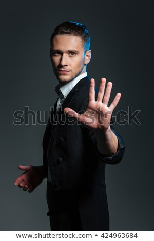 handsome young man magician showing his palm stock photo © deandrobot