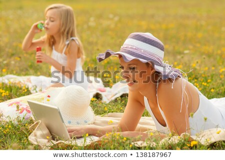 cute young blond having fun with laptop outdoors stock photo © lithian