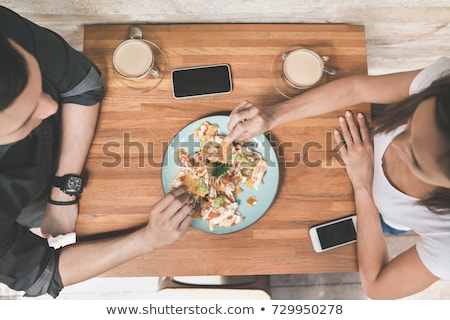 top view of young couple eating in cafe stock photo © deandrobot