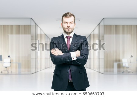 Serious bearded young businessman standing with arms crossed Stock photo © deandrobot