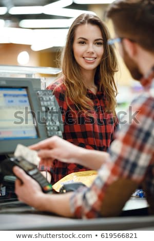 smiling cashier woman on workspace in supermarket shop stock photo © deandrobot
