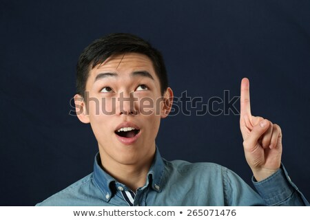Young asian man pointing his forefinger up. Stock photo © RAStudio