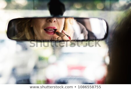 Woman putting on lipstick in car Stock photo © IS2