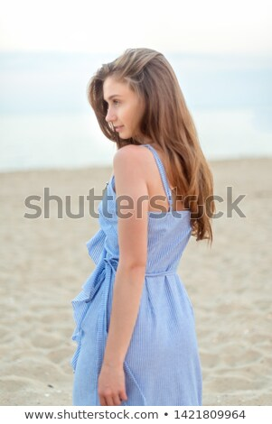 half turn image of caucasian woman with long brown hair holding stock photo © deandrobot