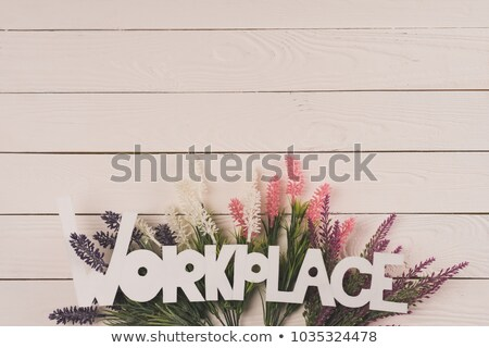 top view of beautiful blooming flowers and word workplace on wooden surface Stock photo © LightFieldStudios