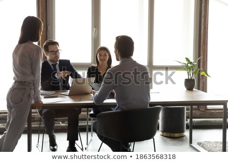 Stock photo: Four young employees sharing opinions and information in the office