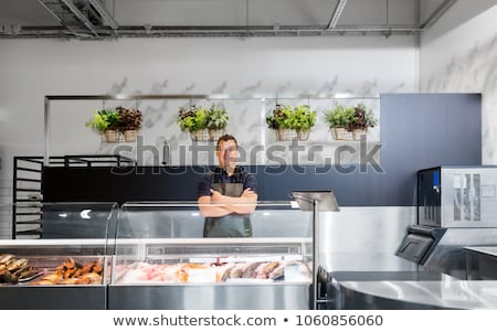 male seller with seafood at fish shop fridge Stock photo © dolgachov