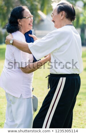 An elderly man wipe the sweat from his wife's face with towel Stock photo © Kzenon