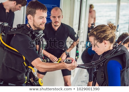 Diving instructor helps a beginner diver prepare for diving Stock photo © galitskaya