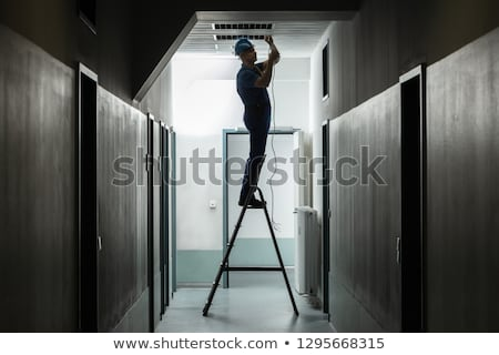 Male Electrician On Step Ladder Installing Light Stock photo © AndreyPopov