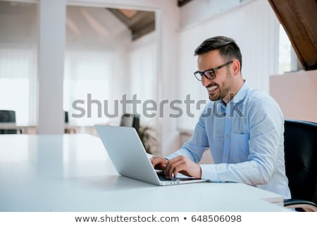 smiling young business man working on laptop computer stock photo © deandrobot