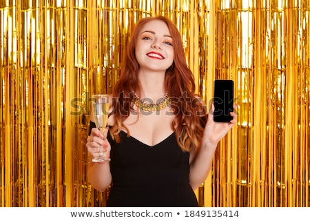 Happy girl in red dress holding phone and glass of champagne on  Stock photo © dashapetrenko