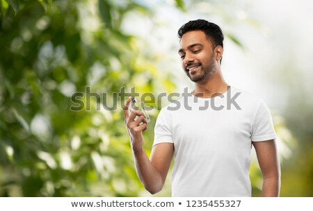 indian man with perfume over natural background Stock photo © dolgachov