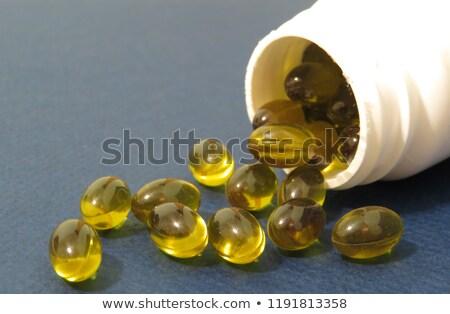 Bottle with gelatin capsules on white Stock photo © dariazu