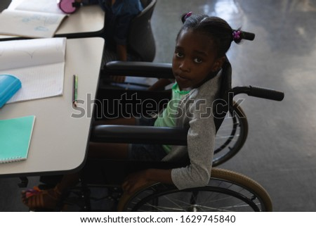 High angle view of disable black schoolgirl looking at camera and sitting at desk in classroom of el Stock photo © wavebreak_media