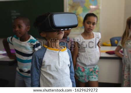 Front view of schoolboy using virtual reality headset whit his classmates behind him in classroom of Stock photo © wavebreak_media