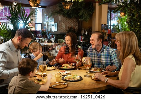 Side view of a multi-generation family having meal on dining table at home Stock photo © wavebreak_media
