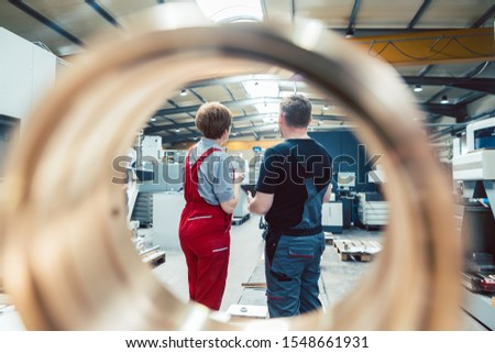 Workers standing on the factory floor seen through a workpiece Stock photo © Kzenon