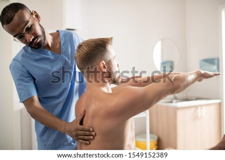 Young mixed-race medical specialist in uniform massaging back of patient Stock photo © pressmaster