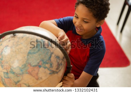 High angle view of playful mixed-race schoolboy studying globe at desk in a classroom at elementary  Stock photo © wavebreak_media