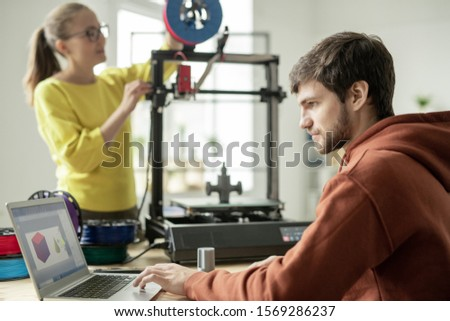 Serious man concentrating on work over new objects on background of colleague Stock photo © pressmaster