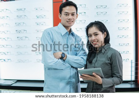 Happy young woman looking at display with eyewear while listening to consultant Stock photo © pressmaster