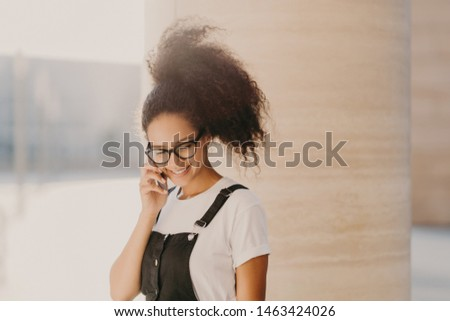 Millennial Afro woman speaks via cell phone, uses roaming connection, looks down, enjoys pleasant co Stock photo © vkstudio