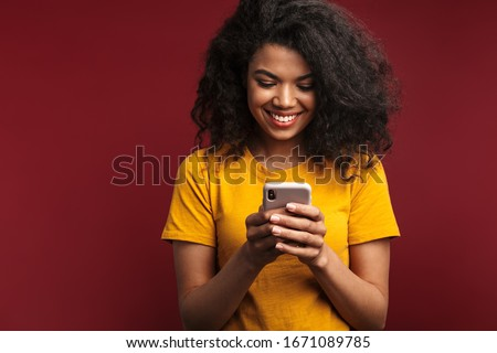 Photo closeup of brunette smiling woman using cellphone and earpods Stock photo © deandrobot