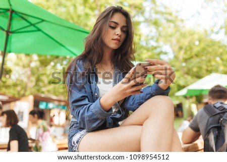 Portrait of dreamy brunette female sits crossed legs on comfortable bed in bedroom, looks thoughtful Stock photo © vkstudio