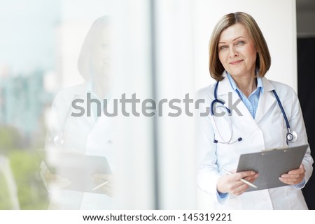 Portrait of matured Caucasian female doctor standing in clinic at hospital. Patient and doctors are  Stock photo © wavebreak_media
