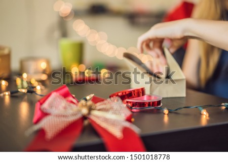 Young woman is packing presents. Present wrapped in craft paper with a red and gold ribbon for chris Stock photo © galitskaya