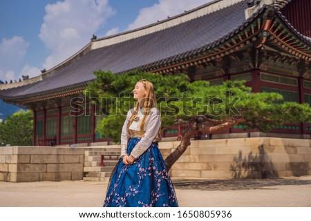 Young caucasian female tourist in hanbok national korean dress at Gyeongbokgung Palace. Travel to Ko Stock photo © galitskaya
